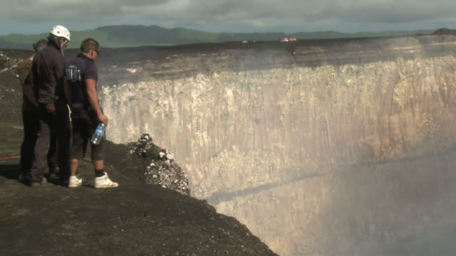 men stand on edge of giant crater at marum volcano, ambrym island, vanuatu - geologist stock videos & royalty-free footage