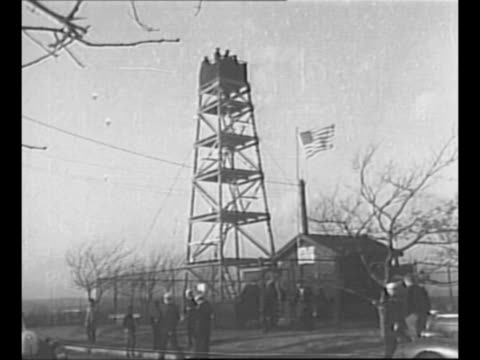 WS men stand on guard tower on Corey Hill in Brookline MA and look through binoculars US flag flies at building at bottom of tower which was built by...
