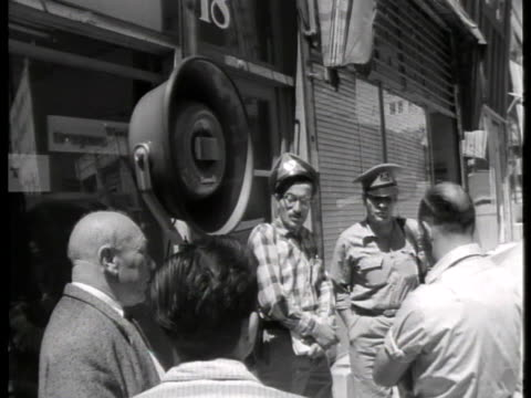 men stand on the streets of jerusalem and listen to the trial of adolf eichmann. - ゲシュタポ点の映像素材/bロール