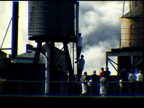 men stand on water tank ladder to watch smoke from collapse. others stand around on roof. shot in manhattan. sound: reporters radio. - world trade center manhattan video stock e b–roll