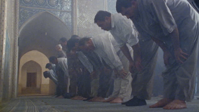 MS men standing and kneeling in row as they pray in Jameh Mosque (Friday Mosque) / Yazd, Iran