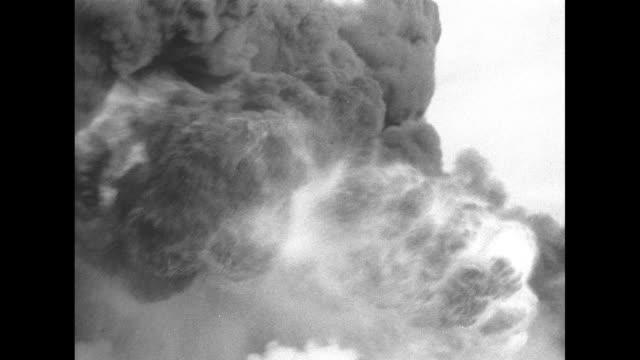 stockvideo's en b-roll-footage met men standing around oil well fire, plume of smoke rising from it / two shots of fire and smoke rising from it / workmen fighting fire / workmen... - fire hose