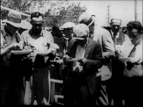 b/w 1931 men standing as they eat at mother jordan's soup kitchen outdoors / san francisco - 1931 stock videos & royalty-free footage