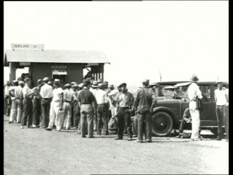 b/w men standing by construction shack, waiting for work / sound - 雇用促進局点の映像素材/bロール
