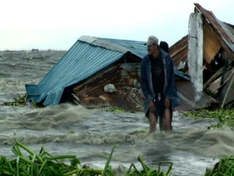 vídeos y material grabado en eventos de stock de men standing in flood waters as they swamp shanty houses; aftermath of typhoon mirinae, philippines - dañado