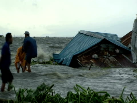 vídeos de stock, filmes e b-roll de men standing in flood waters as they swamp shanty houses; aftermath of typhoon mirinae, philippines, 2009 - acidentes e desastres