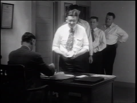 B/W 1932 men standing in line in office receiving scrip from man sitting behind desk / Merced, CA