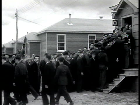 vídeos de stock, filmes e b-roll de men standing in long recruitment line into small building ms recruits in line recruits carry newly issued military clothing supplies out of barracks... - 1943