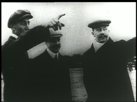 men standing on air field talking + pointing - anno 1903 video stock e b–roll