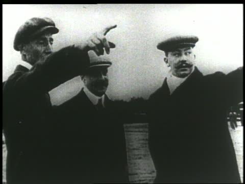 vídeos de stock, filmes e b-roll de b/w 1903 3 men standing on air field talking pointing - orville wright