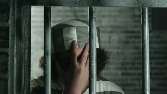 men standing on prison door with his hand on head at prison cell - claustrophobia stock videos and b-roll footage