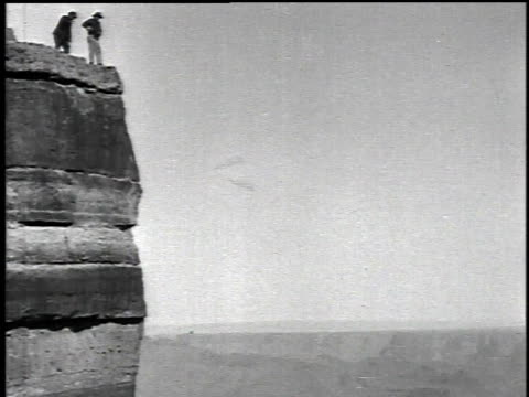 1916 ws men standing on the edge of a cliff and throwing things off / grand canyon, arizona, united states - 1916 stock videos & royalty-free footage