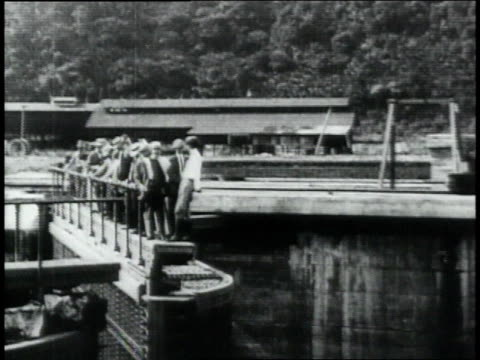 montage men standing on top of canal gate as it opens / republic of panama - anno 1906 video stock e b–roll