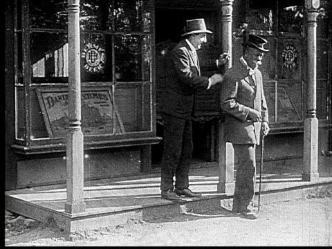 vídeos de stock e filmes b-roll de 1916 b&w ms men standing outside bar smoking and talking  - fato completo