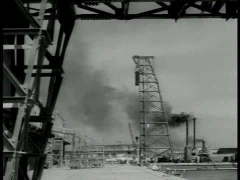 men standing under steel structure of pile driver steam hammer ws equipment dredging harbor by shoreline wrecked buildings bg - pile driver stock videos and b-roll footage