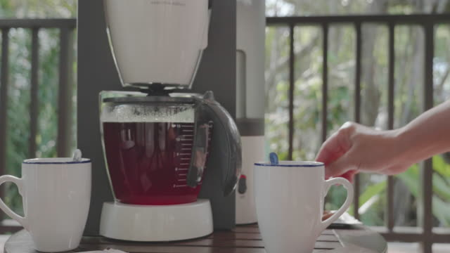 vídeos de stock e filmes b-roll de a men steaming fresh coffee into pot at table of resort in the forest in the morning in the south of thailand. - caixa de fósforos