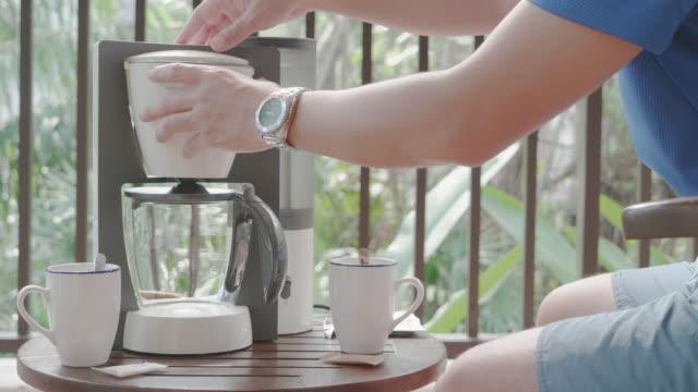 タイ南部の朝、森の中のリゾートのテーブルで鍋に新鮮なコーヒーを蒸している男性。 - マッチ箱点の映像素材/bロール