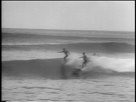 b/w 1966 2 men surfing in surfing competition / one wipes out / hawaii / newsreel - falla av bildbanksvideor och videomaterial från bakom kulisserna