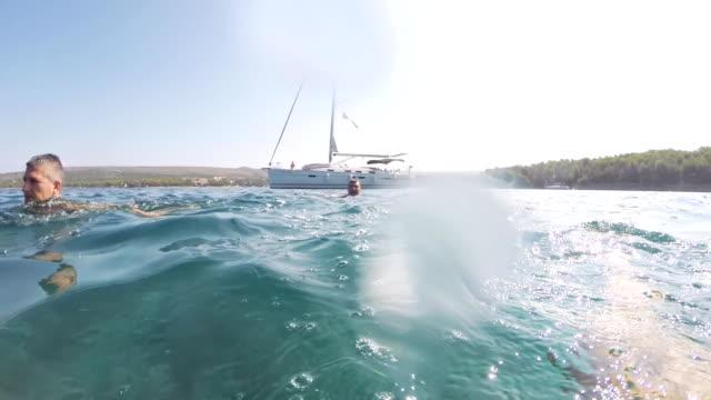 vídeos de stock, filmes e b-roll de slo mo homens de natação fora de um veleiro - ponto de vista de câmera