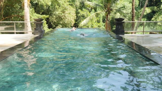 stockvideo's en b-roll-footage met mannen rondjes zwemmen in een zwembad van het resort - buitenbad