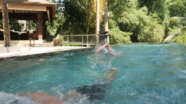 stockvideo's en b-roll-footage met mannen rondjes zwemmen in zwembad van het resort - buitenbad