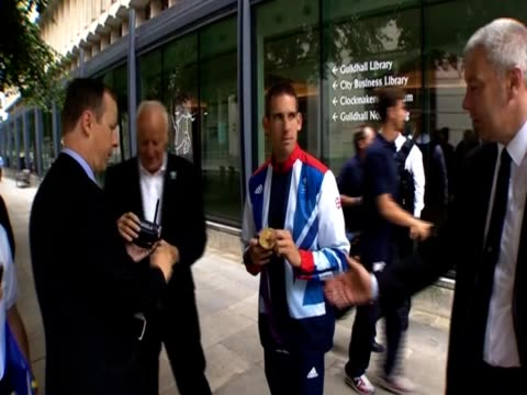 Men take pictures with an Olympics gold medalist before the Team GB bus parade in London