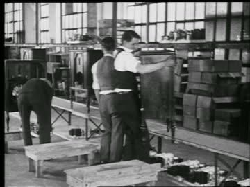b/w 1929 men take radio cabinets from conveyor + assemble radios in factory / philadelphia / indust. - 1920 1929 bildbanksvideor och videomaterial från bakom kulisserna