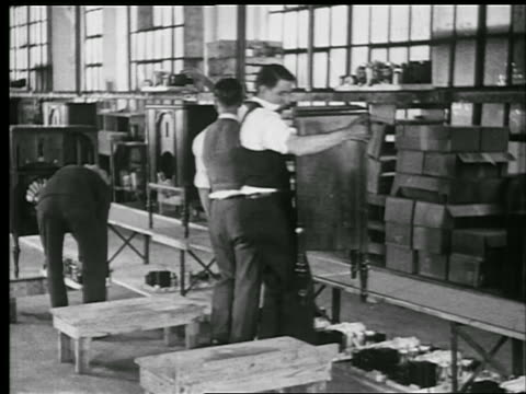 vídeos de stock, filmes e b-roll de b/w 1929 men take radio cabinets from conveyor + assemble radios in factory / philadelphia / indust. - 1920 1929