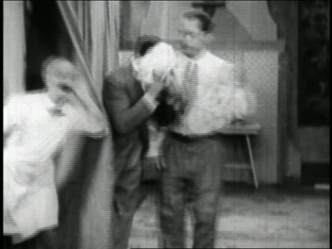 b/w 1928 2 men talking as man comes from behind curtain / knocks one man into bowl of food / short - 1928 stock-videos und b-roll-filmmaterial