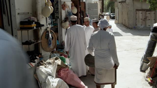 ws men talking outside shop, bahla, oman - 中東点の映像素材/bロール