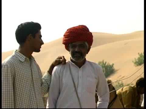 vidéos et rushes de ms men talking, sand dunes in background, rajasthan, india - coiffe traditionnelle