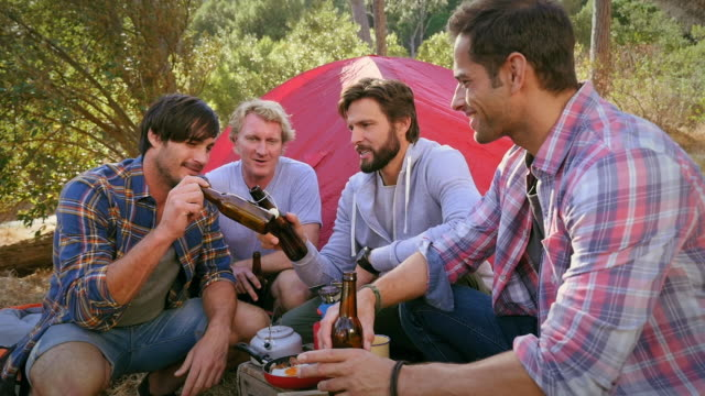 Men talking with beer by tent