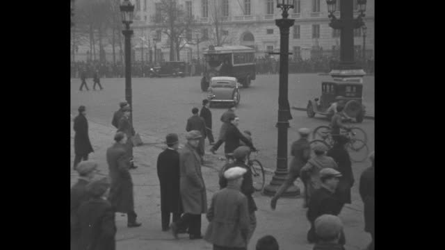 vidéos et rushes de men throw stones at retreating cavalry during riot in paris run toward cavalry / night wounded man lies on street as crowd looks on men hold flares... - 1934