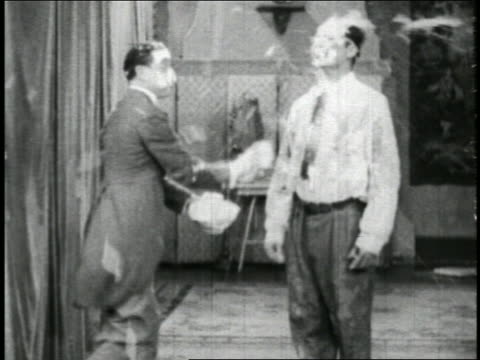 vidéos et rushes de b/w 1928 2 men throwing food at each other in food fight / short - 1928