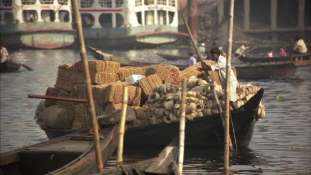 ms, pan, men transporting doormats and yarns in boat on river, dhaka, bangladesh - dhaka stock videos and b-roll footage
