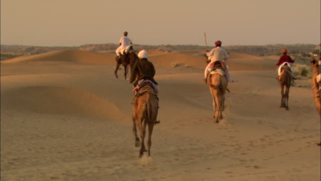 men trot their camels through a desert in india. - camel train stock videos & royalty-free footage