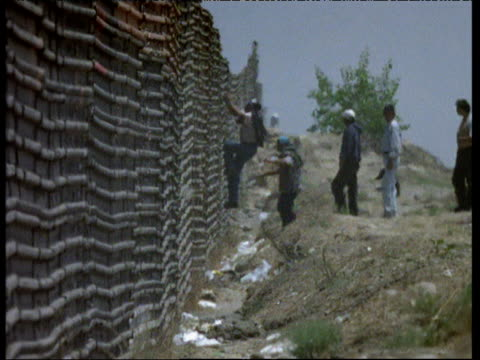 men try to climb border from mexico to usa - emigration and immigration点の映像素材/bロール