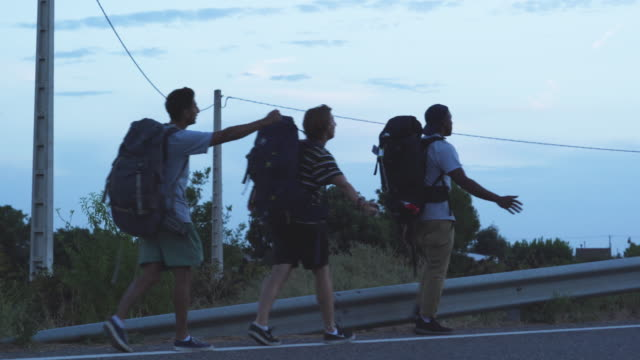 Men try to hitchhike in Spain