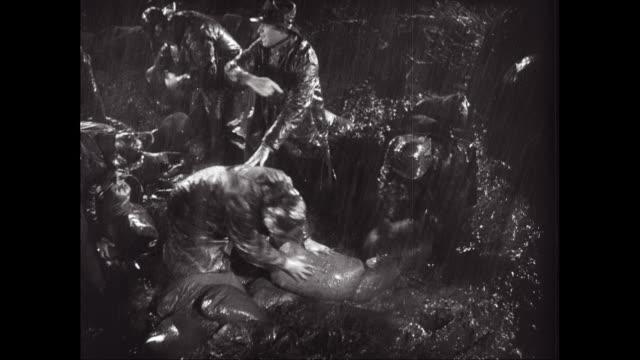 vidéos et rushes de ms men trying to stopping water from river flood / united states - vêtement de pluie