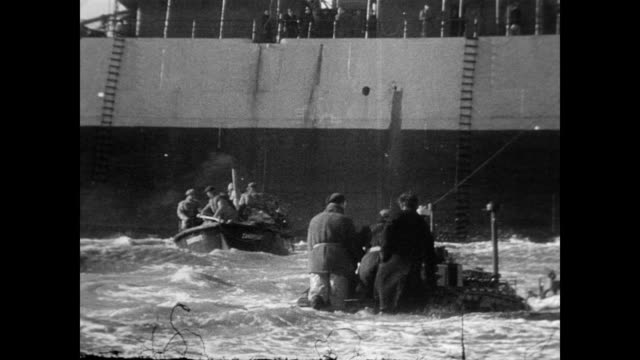 / men trying to walk on a sand laden beach in the middle of a storm in holland / waves crash violently inland as ships bob on the sea / crowd... - 1949 stock videos & royalty-free footage