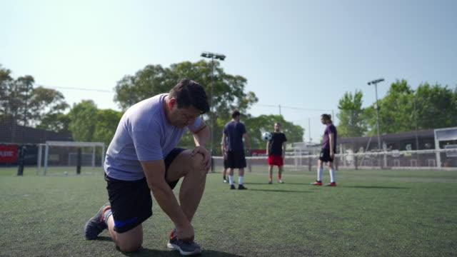 vídeos de stock, filmes e b-roll de homens amarrando cadarço no campo de futebol - termo esportivo