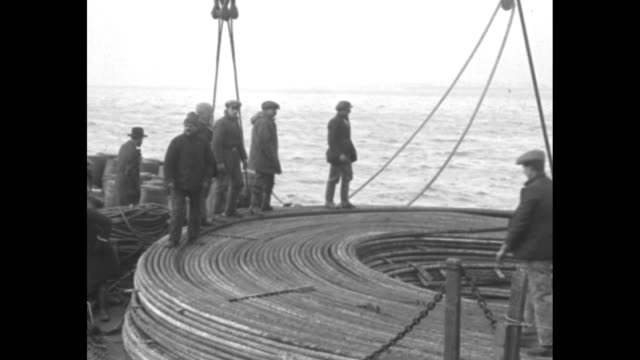 vídeos y material grabado en eventos de stock de men uncoiling cable on ship anchored in ny city harbor / men hauling cable from ship to barge / men coiling up cable on barge / two shots of men... - cable de acero