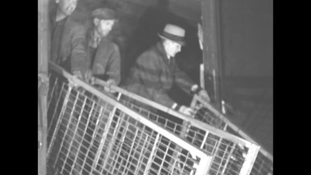 men unload bedsprings from freight car / closer shot / men slide milk cans down ramp from freight car // coast guard boats at night in jersey city nj... - milk churn stock videos & royalty-free footage