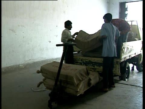 men unload burlap sacks in a warehouse. - 荒い麻布点の映像素材/bロール