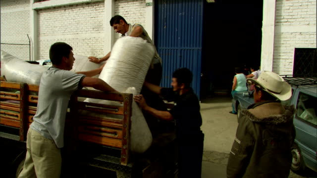 men unload burlap sacks of coffee beans from the back of a truck. - 麻袋点の映像素材/bロール