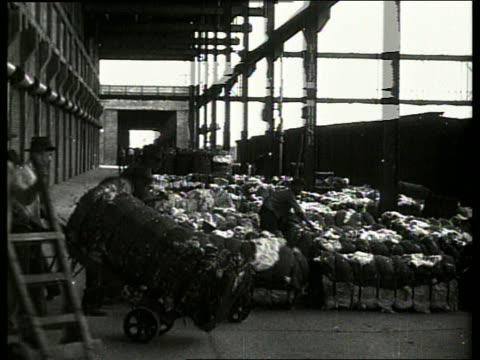 b/w men unloading bales of cotton in warehouse / no sound - 1910年点の映像素材/bロール