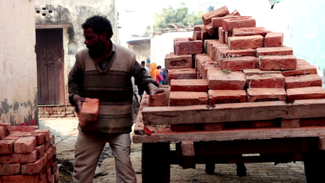 Men unloading bricks from horse cart