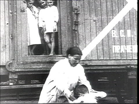 vidéos et rushes de men unloading buckets from the sanitary train ws of dormitory woman helping small children to go down train nurses and doctors examine children kids... - 1910 1919