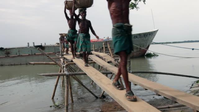 Men unloading goods from a ship, Charkawa village, East Side of Kirtonkhola River, Barisal, Barisal District, Bangladesh, Indian Sub-Continent, Asia.
