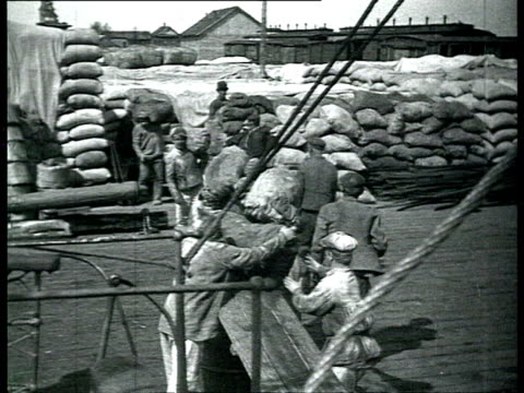 men unloading supplies from steam boat in harbor, passengers embarking onto boat / solovetsky island, russia - 1928 stock-videos und b-roll-filmmaterial